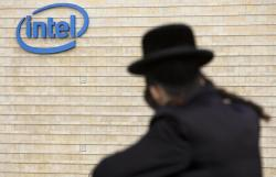 In this Nov. 14, 2009 file photo, an ultra-Orthodox Jewish man is seen next to Intel's office building in Jerusalem. Intel said Monday, May 4, 2020, that it has purchased Israeli urban mobility startup Moovit for $900 million