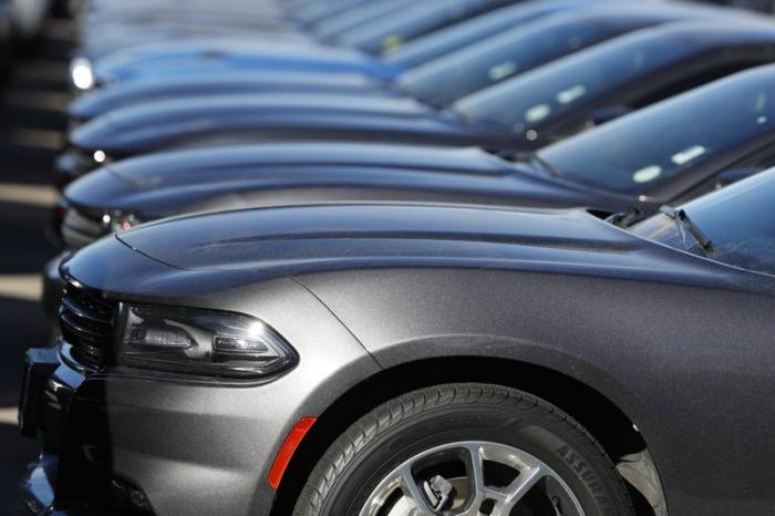 In this Feb. 2, 2020 file photo a long row of unsold Charger sedans sits at a Dodge dealership in Littleton, Colo.