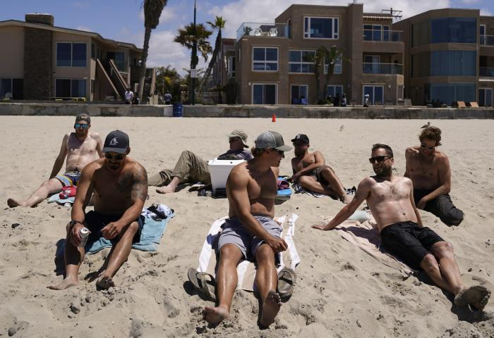 A group of men in town for a bachelor's party sit on the beach Tuesday, April 27, 2021, in San Diego.