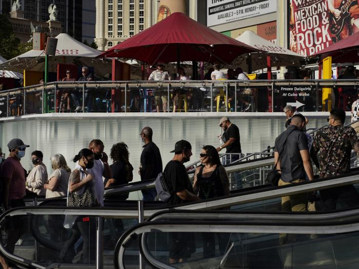 People walk as others dine on the Las Vegas Strip, Saturday, April 24, 2021, in Las Vegas. Las Vegas is bouncing back to pre-coronavirus pandemic levels, with increases in airport passengers and tourism